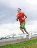 Young man running on a track field.