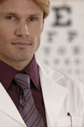 Doctor standing in front of a vision screening chart.