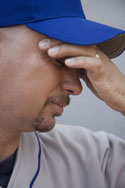 Baseball player holding his head as if he has a headache.