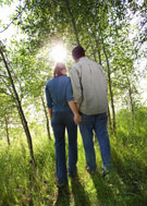 Man and woman holding hands while walking through a wooded area.