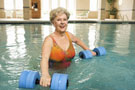 Woman in pool participating in an exercise workout using weights.