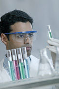 Male lab technician looking at a test tube.