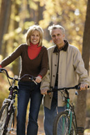 Woman and man walking their bicycles down a path lined with trees.