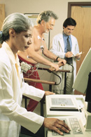 Two medical professionals monitor a man as he walks on a treadmill.