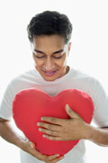 Young man holding a heart shaped pillow.