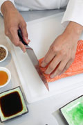 Chef cutting a piece of salmon.
