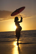 Pregnant woman standing on a beach at sunset.