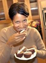 A female holding a plate of cupcakes, while eating one.